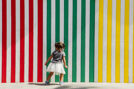 three years old: Three years old girl playing beside striped colored wall of several old beach huts