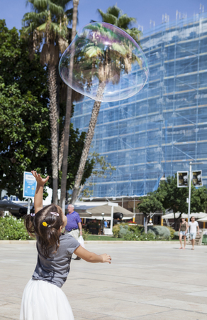three years old: Three years old girl playing in the city with a huge bubble
