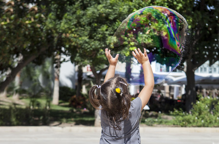 three years old: Three years old girl playing in the city with a huge bubble just before explode it