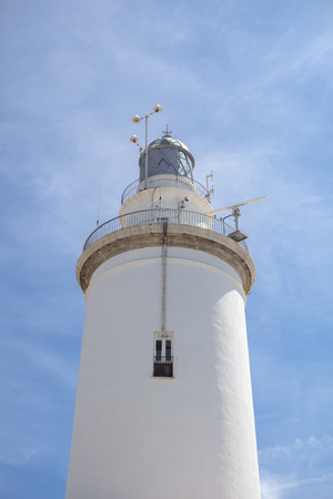 whitewashed: A white whitewashed lighthouse isolated over blue sky with clouds