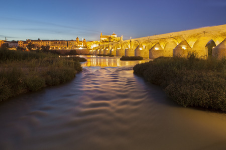 masonary: River Guadalquivir in Cordoba, with roman bridge and Mosque at the bottom, Spain. Night scene Stock Photo