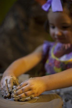 potters wheel: Little girl learning to work with potters wheel