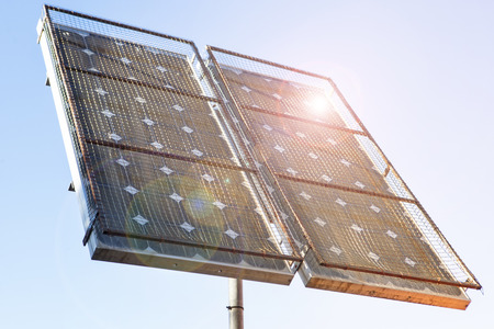 the solar: Solar panel installed in the top of a pole protected with wire netting and illuminated with sun sparkles