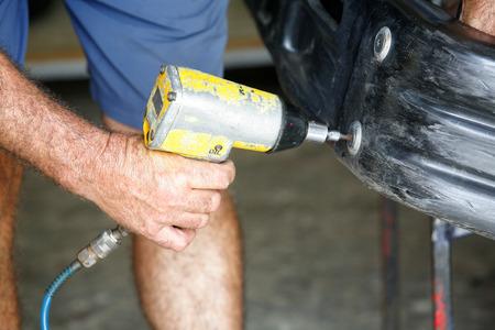 screwing: Car mechanic screwing or unscrewing car bumper with oil pressure gun