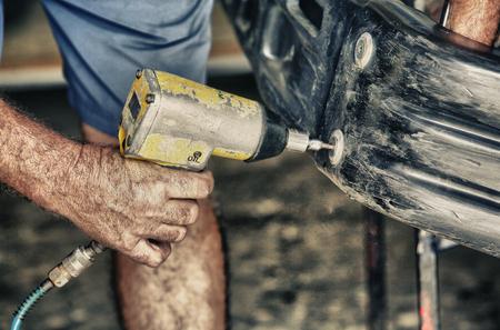 unscrewing: Car mechanic screwing or unscrewing car bumper with oil pressure gun