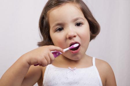 brown eye: Little brown eye girl brushing her teeth. Isolated over white background