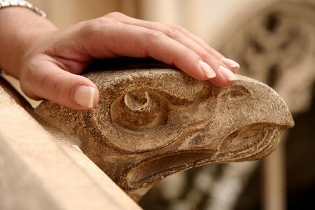 gargouille: A woman hand rest over stone gargoyle. Toledo, Spain
