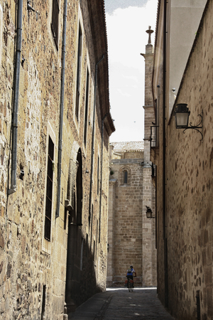 saddlebag: Biker crossing through the narrow streets of Caceres Old Town, Spain