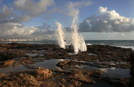 air hole: blow hole on Cadiz coastline sending two burst of water high into the air, Spain