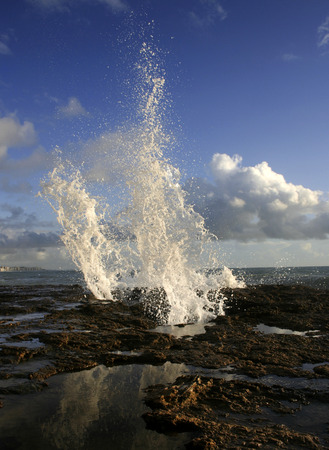 blow hole: blow hole on Cadiz coastline sending two burst of water high into the air, Spain