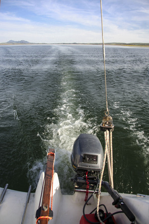 outboard: Sailboat sailing across Alange Reservoir with outboard engine, Spain