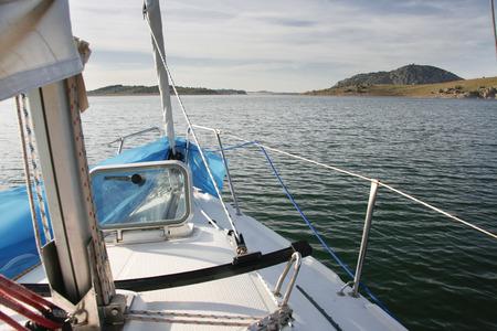 prow: Sailboat sailing across Alange Reservoir, Spain. Prow view