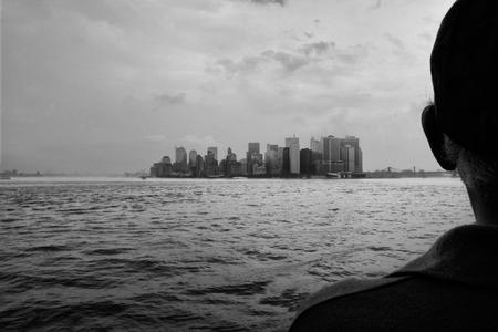 staten: Elder man observes the Manhattan Slyline on board of Staten Island Ferry