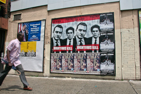 the righteous: HARLEM, NEW YORK CITY, JUNE 2008: Unidentified man walks beside movie posters in Harlemi, on 22 june  2008, in New York City Editorial