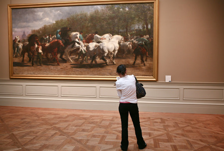 observes: NEW YORK - JUN 25: Girl observes a picture of horses at Museum, June 25, 2008 in New York