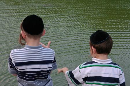 niños judíos con los casquillos lado de un lago en Central Park, Nueva York Foto de archivo