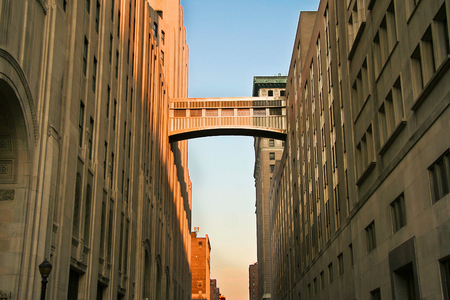 walkway: A walkway connecting two office buildings high above the street. Sunset