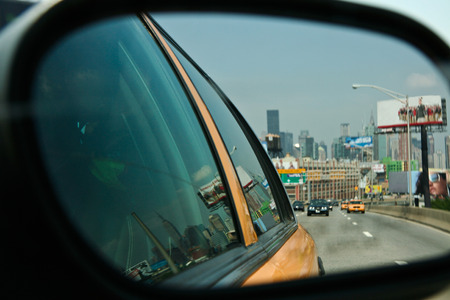 taxicabs: NEW YORK - JUNE 28: New York yellow cabs in motion by a city street scene with the skyline at bottom, reflected in rear mirror. On June 28, 2008, NY, USA