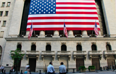 nyse: NEW YORK CITY - JUNE 24: Two men chating under American flag at New York Stock Exchange, in New York City, NY, on June 24, 2008. NYSE is the largest stock exchange in the world counter. Editorial