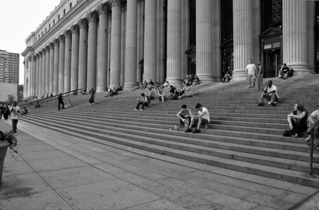 government services: NEW YORK CITY - JUNE 26: People sitting on the stairs of New York General Post Office, in New York City, NY, on June 26, 2008