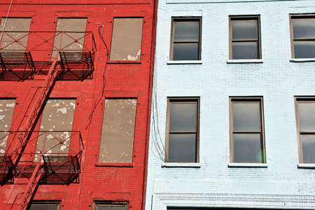 escapes: Colorful apartment buildings facades with emergency escapes. Typical New York City rental complexes with fire escape stairs next to the windows.