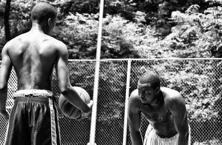 chainlink fence: NEW YORK CITY - JUNE 22: Two black boys playing in one Harlem basketball court, chain-link fence boxes, seen on June 22, 2008 in NY.