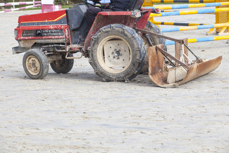 caballo saltando: Smoothing tractor working at horse jumping competition