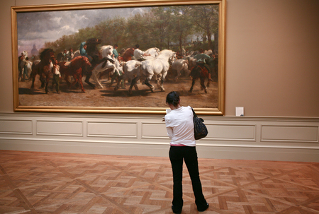 june 25: NEW YORK - JUN 25: Girl observes a picture of horses at Museum, June 25, 2008 in New York
