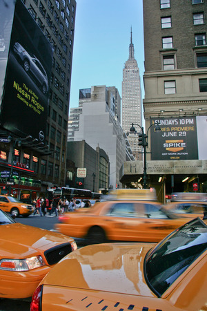 taxicabs: NEW YORK, USA - JUNE 23, 2008: New York yellow cabs in motion by a city street scene with the Empire State building at bottom on June 23, 2008 Editorial