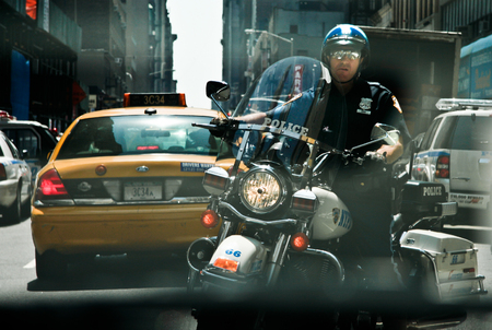 new york times: NEW YORK -JUNE 28: A motorbiker police follow our taxi in Times Square on June 28 2008 in New York. Times Square is one of the most visited tourist attractions in the world. Editorial