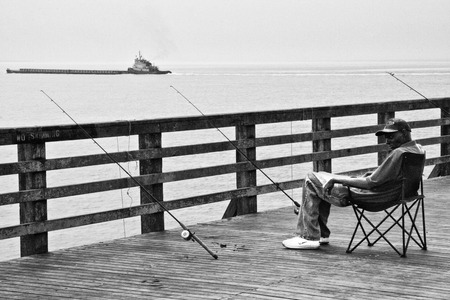 coney: NEW YORK - JUNE 27: Fisherman on a windy day over pier, Coney Island in Brooklyn on June 27, 2008 New York City