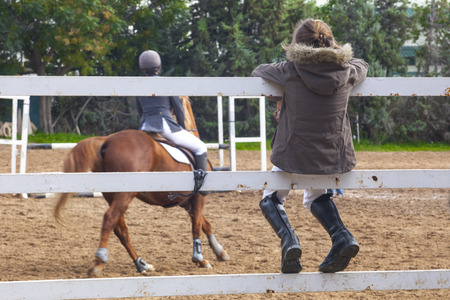 salto de valla: Little girl learning the warming exercise before horse jumping competition. She is sitting over a fence