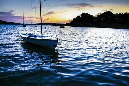 extremadura: Sailboats beside the shore of Alange Reservoir at dusk, Extremadura, Spain Stock Photo