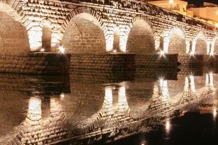 merida: Roman bridge over Guadiana River at night, Merida, Spain