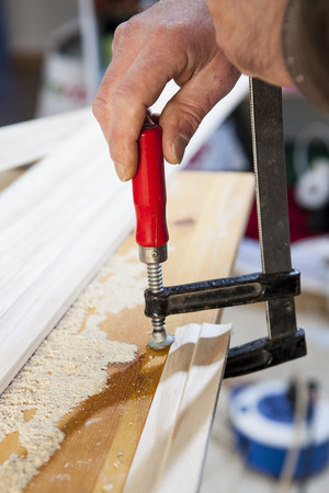 fastening: Carpenter working with doorjambs. He is fastening a clamp