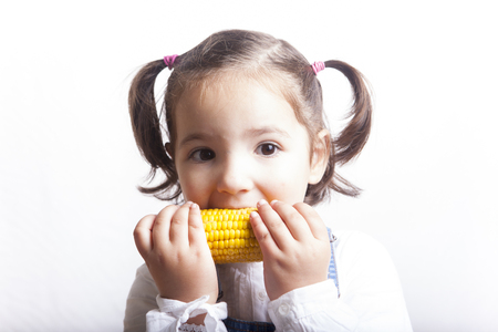 corncob: Portrait of happy girl biting a corncob. Isolated over white background