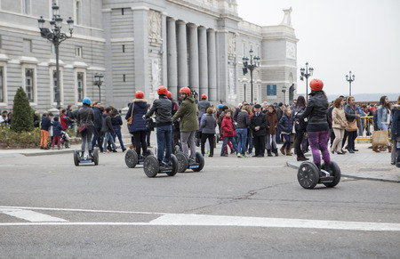 segway: MADRID, SPAIN - DECEMBER 7, 2015: Tourists sightseeing on segway tour of Madrid, Royal Palace, Spain