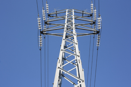 energy needs: High voltage power pylons against blue sky. Low view Stock Photo