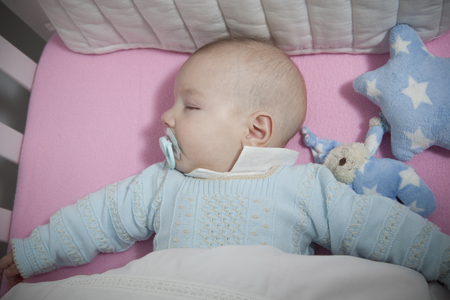four month: Sleeping four month baby boy lying in cot. Overhead view Stock Photo