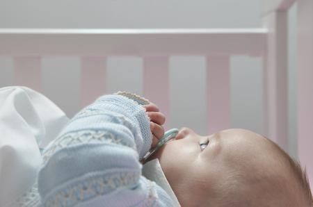 Despierta cuatro meses bebé acostado en la cama con el pacificador. Vista lateral Foto de archivo