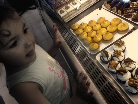 pastry shop: One latin sweet-toothed toddler girl looking sweet in pastry shop