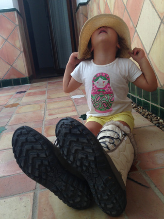 mums: Pretty little girl sitting on curtyard dressed with her mums clothes