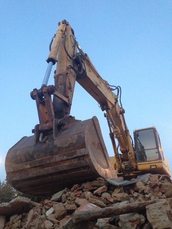loads: Excavator working over loads of brick rubble debris. Low angle Stock Photo
