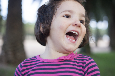 blissfully: Euphoric three years old little girl. Outdoors portrait
