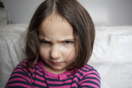 provoked: Angry three years old  little girl, sulking and pouting. Indoors portrait