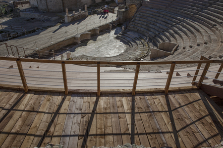 pius: Two people with tourist guide visiting the Roman theatre of Medellin, Spain. High view from grandstand to stage Stock Photo