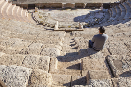 pius: Tourist visiting the Roman theatre of Medellin, Spain. He is sitting on grandstand enjoying a magnificent view