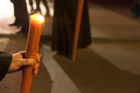bearer: Bearer or nazareno holding large candle at Holy Week Procession, Spain