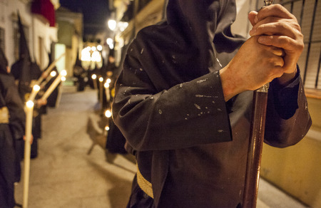 steins: Bearer or nazareno holding a cane with his clothes full of candle wax, Holy Week, Spain Stock Photo