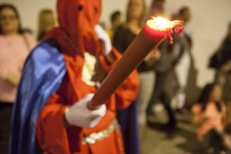 Bearer or nazareno holding large candle at Holy Week Procession, Spain